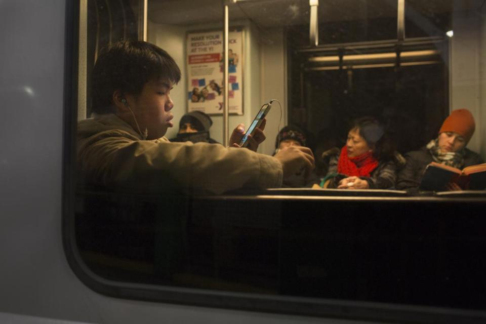 Commuters passed the time riding the T late at night last year.